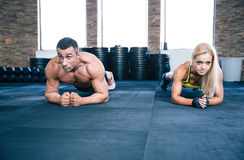 Muscular man and strong woman workout in gym Stock Photo