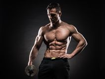Muscular man in studio on dark background Royalty Free Stock Photos