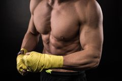Muscular man in studio on dark background Royalty Free Stock Images