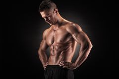 Muscular man in studio on dark background Royalty Free Stock Photography