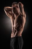 Muscular man in studio on dark background Stock Images