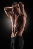 Muscular man in studio on dark background Stock Images