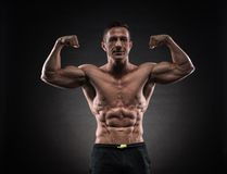 Muscular man in studio on dark background Stock Photography