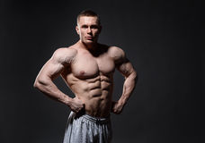 Muscular man in studio over dark background shows royalty free stock photo