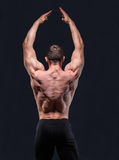 Muscular man in studio show his back with hands royalty free stock image