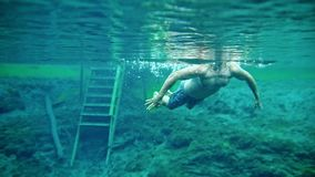 Muscular man swimming underwater in the clear blue lake