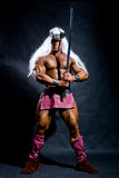 Muscular man with a sword and long white hair Royalty Free Stock Photos