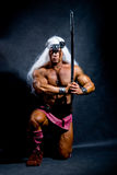 Muscular man with a sword and long white hair. Royalty Free Stock Photography