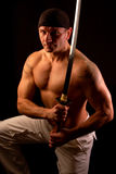 Muscular man with sword Royalty Free Stock Photography