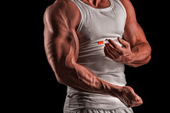 A muscular man with a syringe. Muscular man doing a shot in the biceps, steroids, pharmacology Royalty Free Stock Images