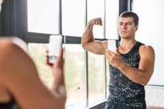 Muscular Man Taking Selfie in Gym stock image