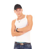 Muscular man in a tank top, jeans and a cap. Young sexy man wearing a white shirt isolated on white Royalty Free Stock Photo