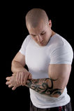 Muscular man with tattoo. Muscular man with a tattoo on his arm flexing his biceps Stock Photos