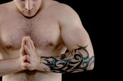 Muscular man with tattoo. Muscular man with a tattoo on his arm flexing his biceps Royalty Free Stock Images