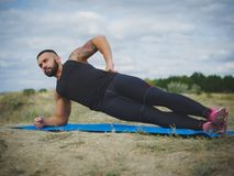 A strong tattooed bodybuilder standing in a side plank on a bank of a river on a blurred natural background. A muscular man with tattoo on his shoulder standing Royalty Free Stock Image