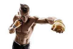 Muscular man throwing a fierce and powerful punch. Royalty Free Stock Photography