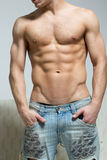 Muscular man in torn jeans stands near the sofa royalty free stock image