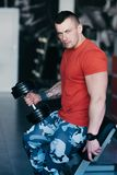 Muscular man training with black dumbbell in the gym. Workout in gym Royalty Free Stock Photography