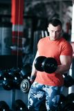 Muscular man training with black dumbbell in the gym. Workout in gym Stock Photo