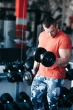Muscular man training with black dumbbell in the gym. Workout in gym Stock Photos