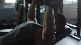 Man is training in gym. Muscular man is training in gym using dumbbells stock video
