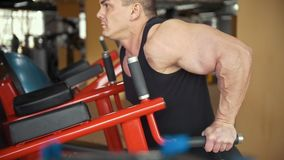 Muscular man training his bicep in a gym. Close up, slow motion stock video footage