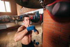 Muscular man training with punching bag. Stock Photo