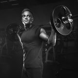 Muscular man training squats with barbells over head royalty free stock photography