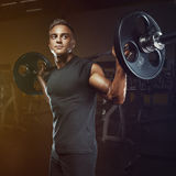 Muscular man training squats with barbells over head royalty free stock images