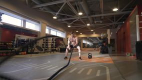 Muscular man training workout exercise with ropes in fitness club. Sport man using fitness rope in functional training. Power and cardio training stock video footage