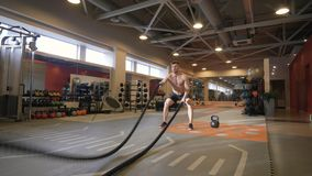 Muscular man training workout exercise with ropes in fitness club royalty free stock images