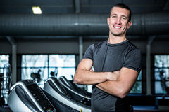 Muscular man on treadmill with crossed arms Stock Photos