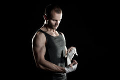 Muscular man, tying an elastic bandage on his hand Royalty Free Stock Images