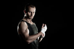 Muscular man, tying an elastic bandage on his hand Stock Image
