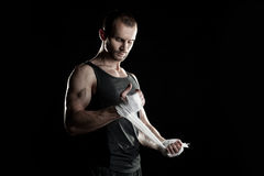 Muscular man, tying an elastic bandage on his hand Royalty Free Stock Image