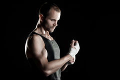 Muscular man, tying an elastic bandage on his hand, black background Stock Photography