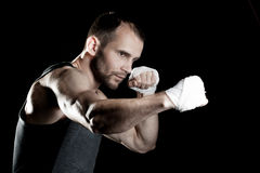 Muscular man, tying an elastic bandage on his hand, black background Royalty Free Stock Photography