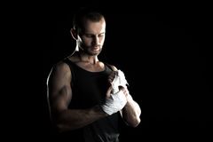 Muscular man, tying an elastic bandage on his hand, black background royalty free stock photo
