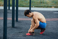 Muscular man tying shoes before exercise at crossfit ground, closeup. Sport concept Stock Photos