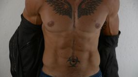 Muscular man undressing, taking off jacket stock video
