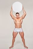 Muscular man uplifting blank circle copy space. Full length attractive bare-chested male in underwear uplifting over his head blank round banner placard with Stock Image