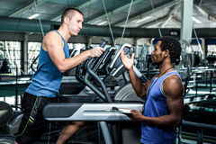 Muscular man using elliptical machine with trainer. Muscular men using elliptical machine with trainer at gym Stock Photography