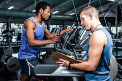 Muscular man using elliptical machine with trainer. Muscular men using elliptical machine with trainer at gym Stock Photos