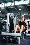 Muscular man using exercise machine for legs Stock Image