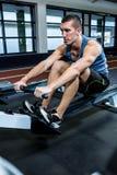 Muscular man using rowing machine Royalty Free Stock Image