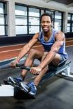 Muscular man using rowing machine Stock Photos
