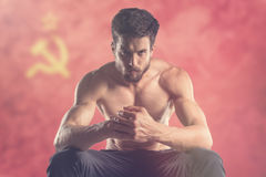 Muscular man with USSR flag behind. Muscular man Royalty Free Stock Photos