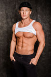 Muscular man  in  vest and  cap with a naked torso. Muscular young sexy man  in a vest and a cap with a naked torso on black background Stock Images