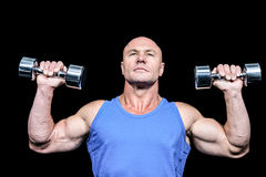 Muscular man in vest lifting dumbells Royalty Free Stock Photography