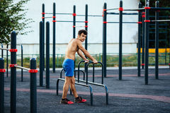 Muscular man warming up before exercise at crossfit ground doing push ups as part of training. Sport concept Royalty Free Stock Image